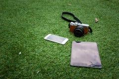 Macchina fotografica, compressa e smartphone su un fondo dell'erba Immagini Stock