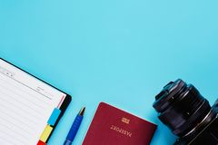 Macchina fotografica con il passaporto, il taccuino e la penna su fondo blu fotografie stock libere da diritti
