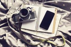 Macchina fotografica d'annata con il telefono cellulare nero in bianco ed il diario in bianco, derisione immagine stock libera da diritti