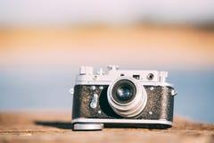 macchina fotografica d'annata del telemetro di Piccolo-formato di 35mm vecchia retro sui bordi di legno anziani Immagini Stock Libere da Diritti