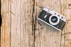 macchina fotografica d'annata del telemetro di Piccolo-formato di 35mm vecchia retro sui bordi di legno anziani Fotografie Stock