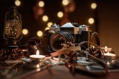 Macchina fotografica d'annata della composizione in Natale vecchia, candele, torcia elettrica su una tavola di legno scura fotografia stock libera da diritti