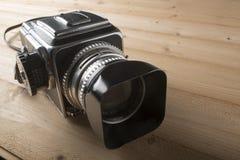 Macchina fotografica d'annata della foto sulla tavola di legno Fotografie Stock