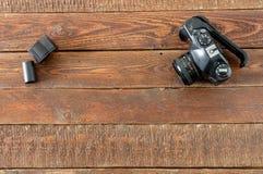 Macchina fotografica d'annata e film sulla tavola di legno Fotografia Stock Libera da Diritti