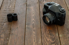 Macchina fotografica d'annata e film sulla tavola di legno Fotografia Stock