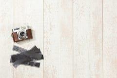 Macchina fotografica d'annata e strisce di pellicola su tavola di pavimento Immagine Stock