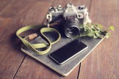 Macchina fotografica d'annata, smartphone in bianco, diario e foglie sulla linguetta di legno fotografia stock libera da diritti