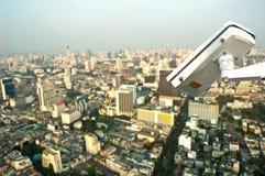 Macchina fotografica del CCTV di sicurezza sul fondo della città Immagine Stock
