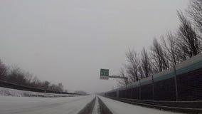 Macchina fotografica del cruscotto in automobile, neve sulla strada principale stock footage