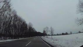 Macchina fotografica del cruscotto in automobile, neve sulla strada principale archivi video