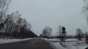 Macchina fotografica del cruscotto in automobile, neve sulla strada principale video d archivio