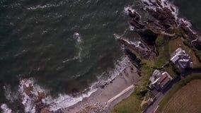 Macchina fotografica del fuco che osserva giù le rocce e la linea costiera della Cornovaglia video d archivio