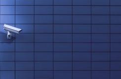 Macchina fotografica del monitoraggio di sorveglianza contro una parete blu Fotografie Stock Libere da Diritti
