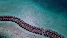 Macchina fotografica del quadrato che vola su sopra i bungalow all'isola delle Maldive video d archivio