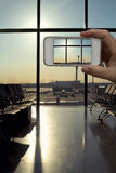 Macchina fotografica del telefono cellulare che prende pic dell'aeroporto moderno del salotto di partenza Fotografie Stock