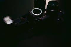 Macchina fotografica della foto DSLR con un insieme di retro lente e flash su un fondo nero con struttura di legno Fotografie Stock Libere da Diritti
