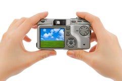 Macchina fotografica della foto nelle mani e nel paesaggio (la mia foto) Fotografie Stock