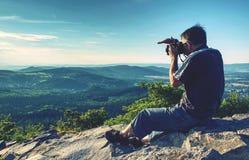 Macchina fotografica della tenuta dell'uomo agli occhi sulla montagna fotografia stock libera da diritti