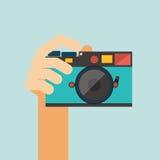 Macchina fotografica della tenuta della mano su fondo blu illustrazione di stock