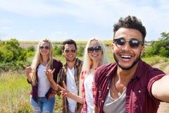 Macchina fotografica dello Smart Phone della tenuta dell'uomo che prende ad amici della foto del selfie fine di sorriso del front Fotografia Stock Libera da Diritti