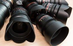 Macchina fotografica di Digital SLR ed alcune lenti manuali intercambiabili L'attrezzatura per cineasta La Tabella di legno Fotografie Stock