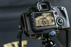 Macchina fotografica di DSLR che prende una macro foto delle monete di Bitcoin Bitcoin sotto l'occhio del concetto di governo fotografie stock libere da diritti