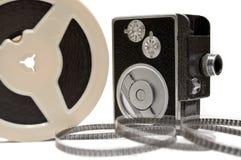Macchina fotografica di film domestico e bobina di pellicola isolata su bianco Fotografia Stock