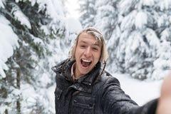 Macchina fotografica di sorriso del giovane che prende la foto di Selfie nella neve Forest Guy Outdoors di inverno immagini stock libere da diritti