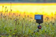 Macchina fotografica digitale compatta sul treppiede con erba nel campo o nel prato Immagine Stock