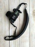 Macchina fotografica digitale con l'imbracatura nera su una tavola di legno Fotografia Stock Libera da Diritti
