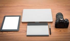 Macchina fotografica digitale di DSLR con il computer portatile del taccuino e della compressa Fotografia Stock