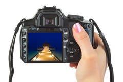 Macchina fotografica a disposizione e paesaggio della spiaggia Fotografia Stock
