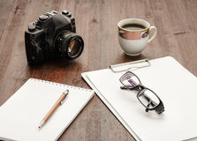 Macchina fotografica e caffè sulla tavola di lavoro Vetri e penna su documento Immagine Stock
