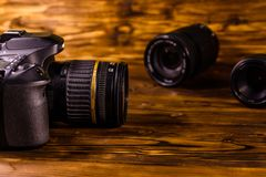 Macchina fotografica e lenti moderne del dslr sulla tavola di legno immagini stock libere da diritti