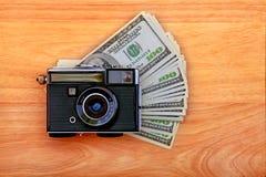 Macchina fotografica e soldi dell'annata fotografia stock