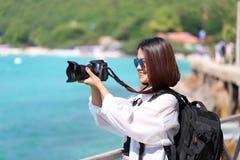 Macchina fotografica felice della tenuta della ragazza dei pantaloni a vita bassa in sue mani con pict di conversazione fotografia stock libera da diritti