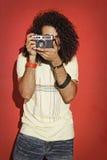 Macchina fotografica lunga della tenuta dei capelli ricci del fotografo appassionato Fotografia Stock