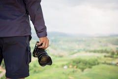 Macchina fotografica professionale del dslr della tenuta della mano del fotografo Fotografia Stock