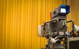 Macchina fotografica professionale e tende gialle chiuse. Fotografia Stock