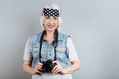 Macchina fotografica senior abbastanza sorridente della tenuta della donna Immagine Stock