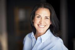 Macchina fotografica spagnola matura di Smiling At The della donna di affari all'ufficio Immagini Stock Libere da Diritti