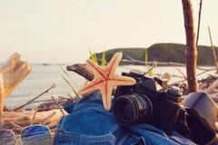Macchina fotografica, stelle marine, jeans rivestimento e vetri di sole su una spiaggia in sole fotografia stock