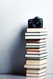Macchina fotografica su un'alta pila di libri Fotografia Stock
