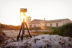Macchina fotografica su un treppiede che fotografa il tramonto Immagini Stock