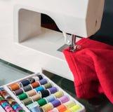 Macchina per cucire bianca e panno rosso Fotografie Stock Libere da Diritti