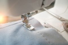 Macchina per cucire e oggetto di abbigliamento blu Primo piano di cucito della gonna L'ago della macchina per cucire ha conficcat fotografie stock libere da diritti