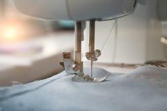 Macchina per cucire e oggetto di abbigliamento blu Primo piano del meccanismo della macchina per cucire di cucito e della gonna L immagini stock