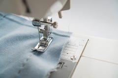 Macchina per cucire e oggetto di abbigliamento blu Primo piano del meccanismo della macchina per cucire di cucito e della gonna L fotografie stock