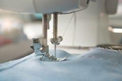 Macchina per cucire e oggetto di abbigliamento blu Primo piano dell'ago della macchina per cucire e del piede del presser L'ago d fotografie stock libere da diritti