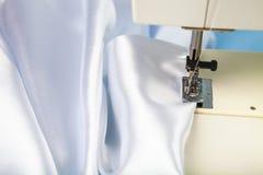 Macchina per cucire e raso bianco fotografia stock